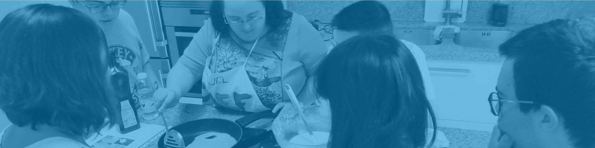Grupo de chicos y chicas con Síndrome de Down cocinan juntos guiados por profesora