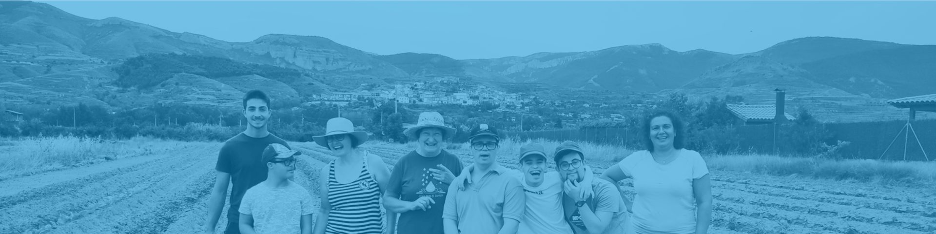 Grupo de personas sonrientes está en un campo labrado con sombreros de paja